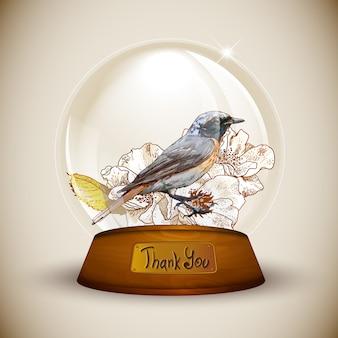 Globo de cristal con flor y pájaro.
