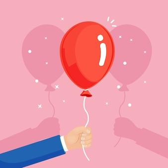 Globo de helio rojo en la mano, bolas de aire volando sobre fondo blanco. feliz cumpleaños, vacaciones