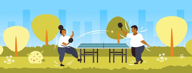 Gordo obeso pareja jugando ping pong tenis de mesa afroamericano sobrepeso hombre mujer divirtiéndose concepto de pérdida de peso parque público paisaje