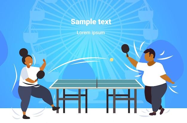 Gordo obeso pareja jugando ping pong tenis de mesa afroamericano sobrepeso hombre mujer divirtiéndose concepto de pérdida de peso parque público rueda de la fortuna copia espacio