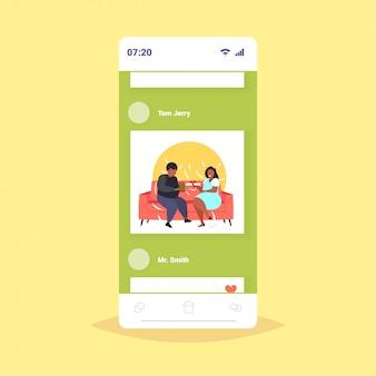 Gordo sobrepeso pareja dando sorpresas cajas de regalo entre sí obeso mezclar raza hombre mujer sentada en el sofá vacaciones celebración obesidad concepto teléfono inteligente pantalla aplicación móvil en línea