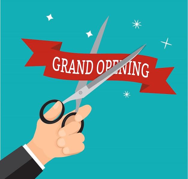 La gran apertura roja de la cinta del corte del negocio de la mano con scissor.