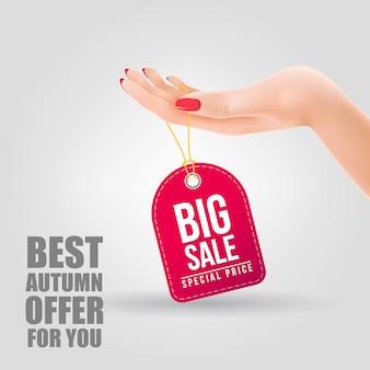 Gran venta, letras de precio especial en la etiqueta que cuelga en la mano