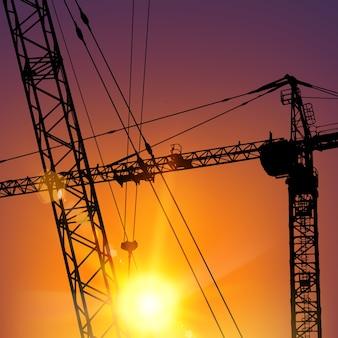 Grúa torre de gran altura que levanta la carga durante la puesta de sol.