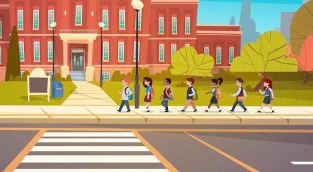 Grupo de alumnos mezcla raza caminar a la escuela edificio primaria escolares estudiantes