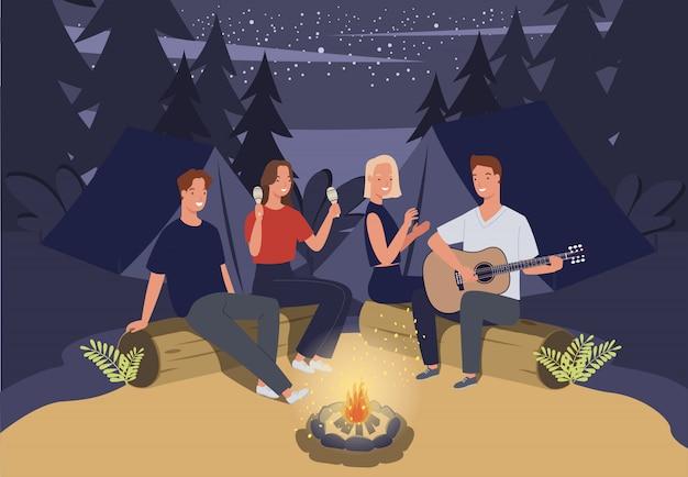 Grupo de amigos acampando. están sentados alrededor de la fogata y tocando la guitarra.