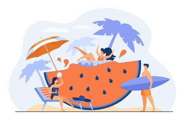 Grupo de amigos disfrutando de las actividades de verano, divirtiéndose en la playa o en la piscina, bebiendo cócteles, flotando con un anillo de goma en una enorme rebanada de sandía. vacaciones, viajes, concepto de ocio.