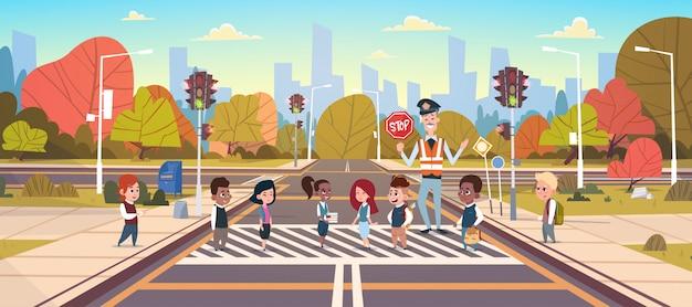 Grupo de ayuda de guardia de policía de niños de la escuela cruzando la carretera