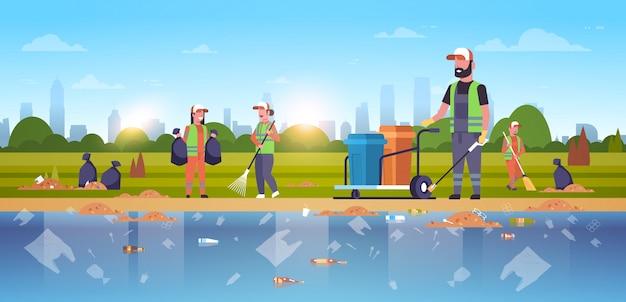 Grupo de conserjes reuniendo equipo de limpieza de basura en uniforme trabajando juntos en el área de playa servicio de limpieza concepto de mejora ambiental fondo de paisaje urbano de banco público de río horizontal