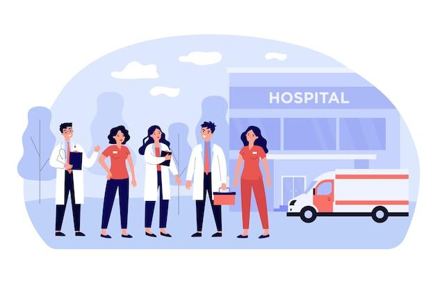 Grupo de dibujos animados de médicos y farmacéuticos cerca del edificio del hospital