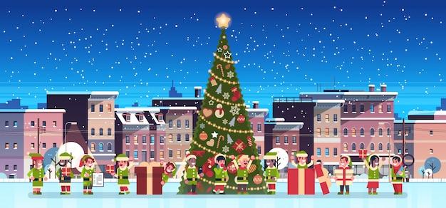 Grupo de elfos cerca de abeto decorado ciudad edificio casas noche invierno
