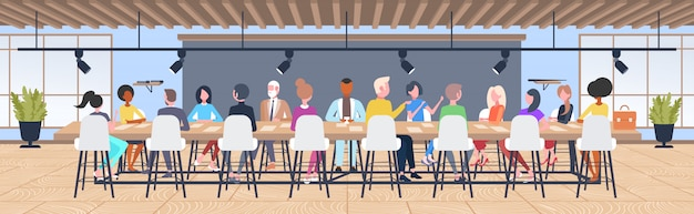 Grupo de empresarios lluvia de ideas sentado en la mesa redonda durante la reunión de la conferencia compañeros de trabajo de raza mixta discutiendo nuevo proyecto en co-working espacio abierto interior horizontal