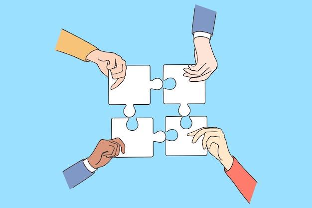 Grupo de empresarios socios colegas manos tratando de conectar las piezas del rompecabezas en la oficina