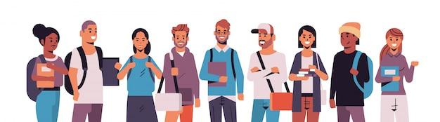 Grupo de estudiantes sosteniendo libros mezclar raza chicas y chicos con mochilas de pie juntos concepto de educación retrato de personajes de dibujos animados masculinos femeninos