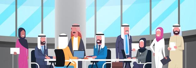 Grupo de felices sonrientes árabes empresarios trabajando juntos en la oficina siéntese en el escritorio equipo de trabajadores musulmanes reunión de lluvia de ideas