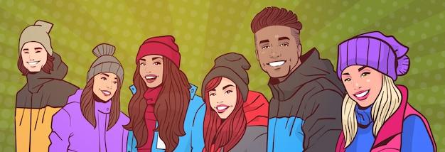 Grupo de gente joven feliz sonriente mezcla raza en ropa de invierno sobre colorido estilo retro fondo horizontal