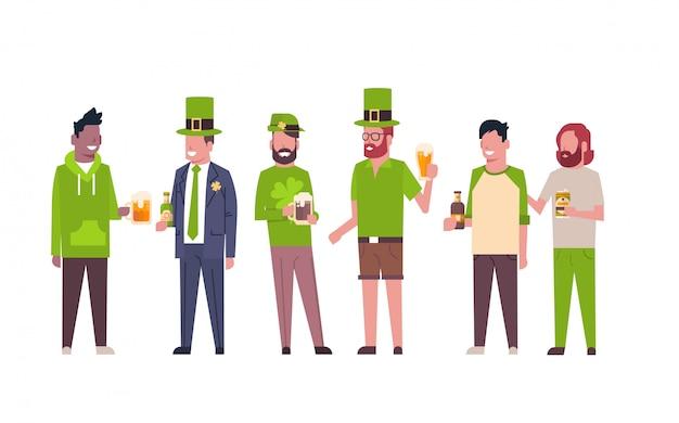 Grupo de hombres de raza mixta en ropa verde beber cerveza celebrando feliz día de san patricio aislado
