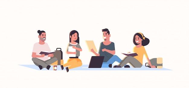 Grupo de jóvenes estudiantes adolescentes sentados juntos amigos de la universidad relajantes y hablando concepto de educación plana hembra personajes de dibujos animados masculinos horizontal longitud completa