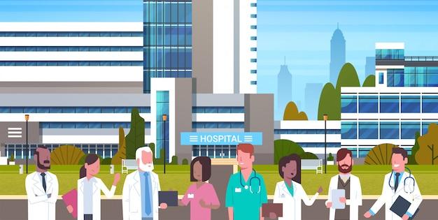 Grupo de médicos que se colocan en frente del exterior del edificio del hospital