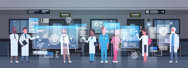Grupo de médicos que utilizan un monitor digital que trabaja en medicina hospitalaria y tecnología moderna