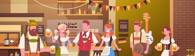 Grupo de personas beben cerveza en el bar oktoberfest fiesta celebración hombre y mujer vistiendo ropas tradicionales concepto fest