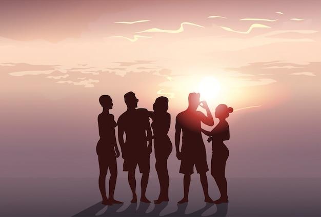 Grupo de personas de silueta stand hombre y mujer de cuerpo entero sobre fondo de puesta de sol