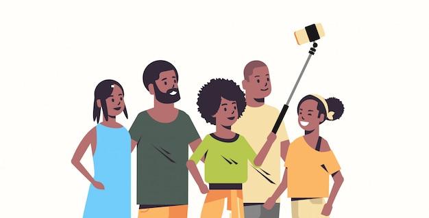 Grupo de personas usando selfie stick hombres mujeres tomando fotos en la cámara del teléfono inteligente amigos divirtiéndose retrato de personajes de dibujos animados femenino masculino horizontal