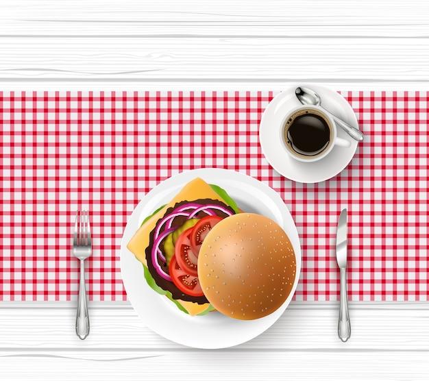 Hamburguesa y taza de café negro en la mesa de madera