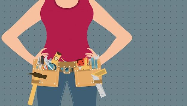 Handywoman con las manos en la cintura y cinturón de herramientas