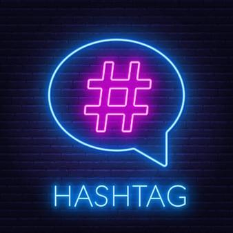 Hashtag de neón en bocadillo de diálogo sobre fondo de pared de ladrillo.