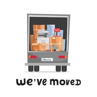 Hemos movido el concepto de letras a mano. muebles de oficina y equipos en la parte trasera de un camión. vista trasera del camión. pila de cajas de cartón con silla, impresora, planta y montones de papel.