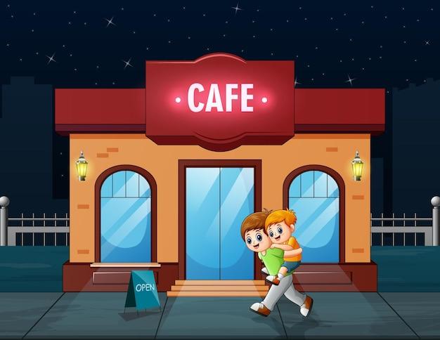Un hermano sosteniendo a su hermano menor frente al café.