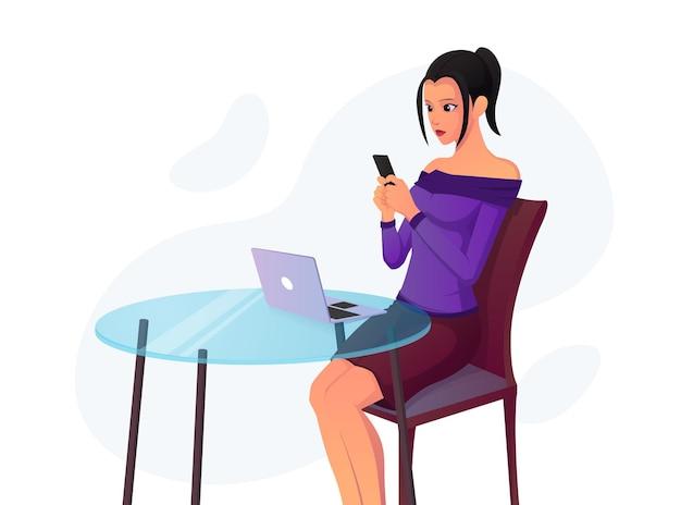Hermosa chica enviando mensajes de texto en su teléfono mientras está sentada en una silla frente a su computadora portátil