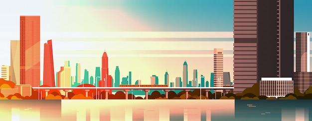 Hermosa ciudad en el panorama de la puesta del sol con altos rascacielos y el paisaje urbano de metro sobre el agua
