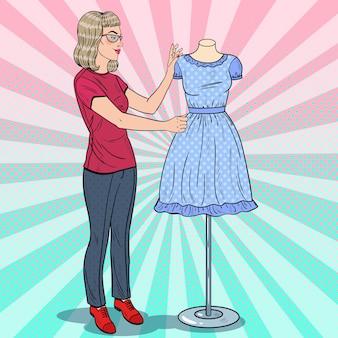 Hermosa diseñadora de moda con vestido en un maniquí