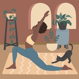 Hermosa jovencita haciendo práctica de yoga en su cómodo apartamento, con gato negro. posturas de asana y meditación.