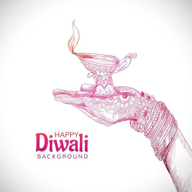 Hermosa mano sujetando el festival de diwali de lámpara de aceite indio