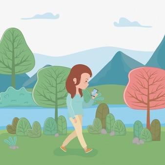Hermosa mujer caminando en el parque con teléfono inteligente