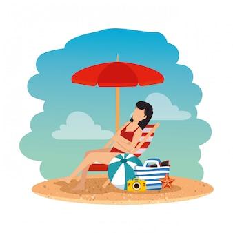 Hermosa mujer con traje de baño sentado en una silla de playa y una bolsa en la playa