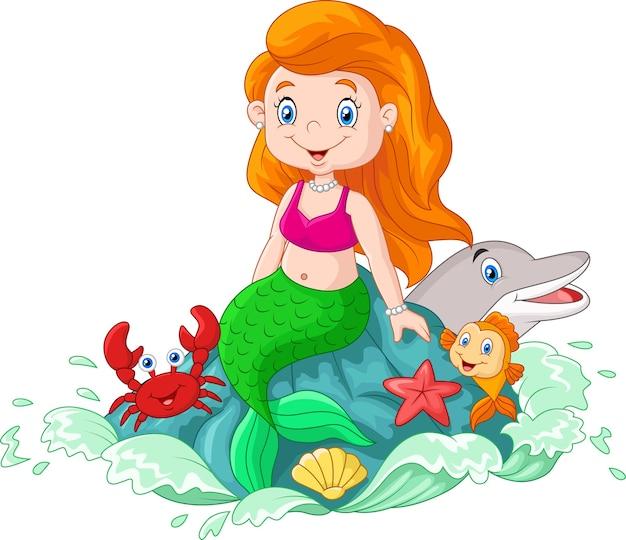 Hermosa sirena sentada en la roca en el mar