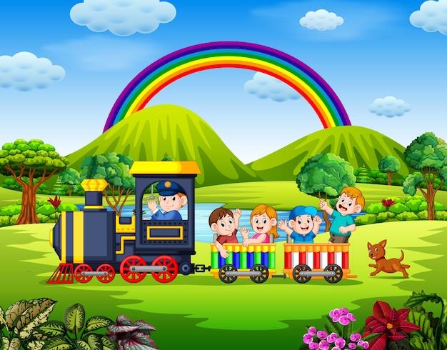 Hermosa vista con los niños dentro del tren ondeando bajo el arcoiris.