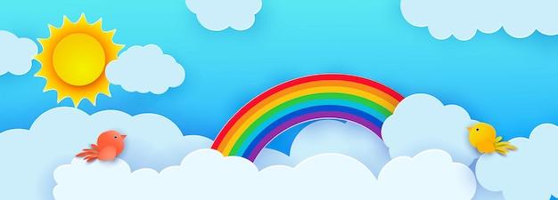 Hermosas nubes mullidas contra un cielo azul con el sol de verano, pájaros y un arco iris.