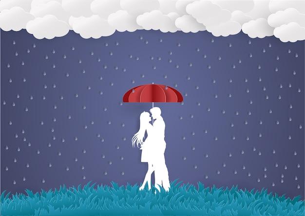 Hierba verde, lluvia y joven abrazo a su amante con un paraguas rojo