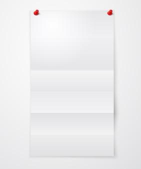 Hoja de papel doblada en blanco con chinchetas.