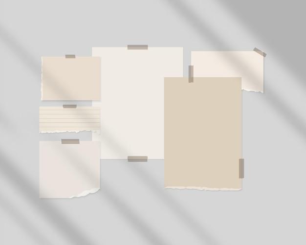 Hojas vacías de papel blanco en la pared con superposición de sombras