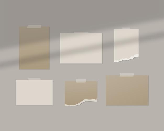 Hojas vacías de papel blanco en la pared con superposición de sombras.