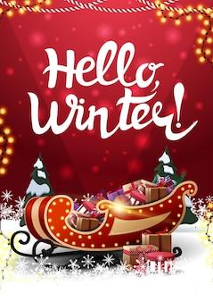 Hola, invierno, postal roja vertical con ventisqueros, pinos, guirnaldas y trineo de santa con regalos