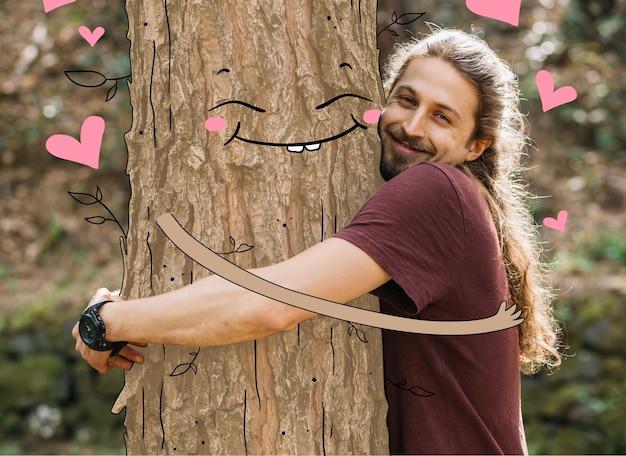 Hombre abrazando un árbol feliz