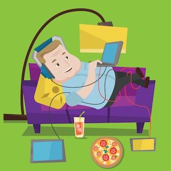 Hombre acostado en el sofá con muchos gadgets.