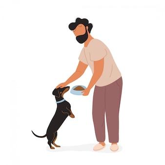 Hombre alimentando y acariciando dachshund